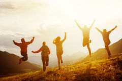 Group of happy friends run and jump. Group of five happy friends is running and jumping in sunset light on background of mountains. Happiness and friendship royalty free stock photo