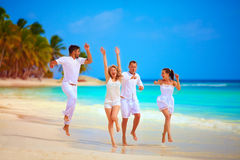 Group of happy friends running on tropical beach, summer vacation royalty free stock photography