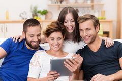 Group of happy friends sharing a tablet. Group of happy young men and women sitting on a sofa together sharing a tablet computer and reading information on the Stock Images