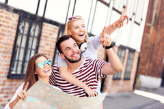 Group of happy friends sightseeing with map Royalty Free Stock Photo