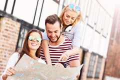Group of happy friends sightseeing with map Stock Photography