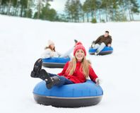 Group of happy friends sliding down on snow tubes Royalty Free Stock Photos