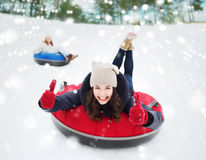 Group of happy friends sliding down on snow tubes Royalty Free Stock Image