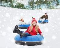 Group of happy friends sliding down on snow tubes stock photos