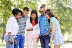 Group of happy friends with smartphone outdoors stock images