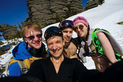 Group of happy friends snowboarding doing selfie. At winter resort royalty free stock photo