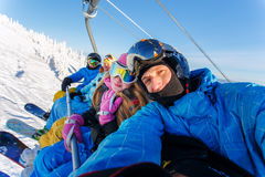 Group of happy friends snowboarding doing selfie. At winter resort royalty free stock photography