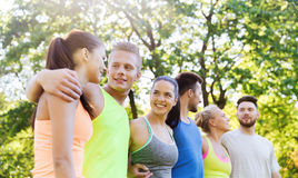 Group of happy friends or sportsmen outdoors. Fitness, sport, friendship and healthy lifestyle concept - group of happy teenage friends or sportsmen hugging and Royalty Free Stock Photos