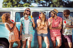 Group of happy friends standing with ice lolly in front of camper van Royalty Free Stock Images
