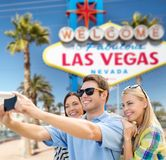 Group of happy friends taking selfie by cell phone. Travel and tourism concept - group of happy friends taking selfie by cell phone over welcome to fabulous las stock photography