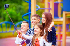 Group of happy friends taking selfy on smart phone, outdoor playground Royalty Free Stock Images
