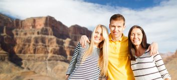Group of happy friends. Tourism, travel and summer holidays concept - group of happy friends over grand canyon national park background stock image