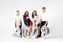 Group of happy friends of two girls and two guys dressed in stylish clothes are holding balloons in the shape of numbers. 2019 on a white background in the stock image