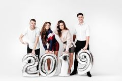 Group of happy friends of two girls and two guys dressed in stylish clothes are holding balloons in the shape of numbers. 2019 on a white background in the stock photography