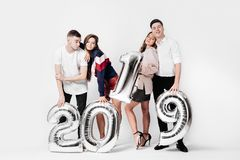 Group of happy friends of two girls and two guys dressed in stylish clothes are holding balloons in the shape of numbers. 2019 on a white background in the royalty free stock photos