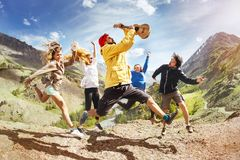 Group of happy friends music jumps trekking fun. Group of happy friends with ukulele guitar is having fun and jumps against mountain during trekking. Music fun royalty free stock photos