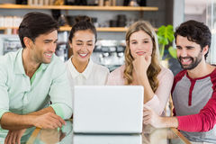 Group of happy friends using laptop Stock Photography