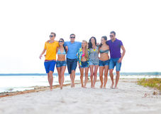 Group of happy friends walking along beach Royalty Free Stock Photo