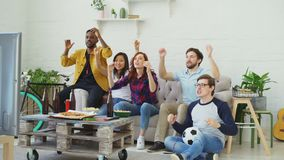 Group of happy friends watching sports game on TV at home. They cheering up favorite team and clapping hands. Group of happy friends watching sports game on TV stock video footage