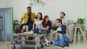 Group of happy friends watching sports game on TV at home. They are happy about their favorite team win competition. Group of happy friends watching sports game stock video