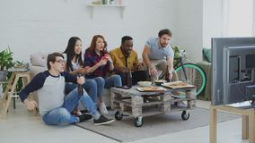 Group of happy friends watching sports game on TV at home. They jumping and yelling while their favorite team win. Group of happy friends watching sports game on stock footage