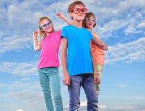 Group of happy friends wearing eyeglassesahainst blue sky Stock Photo