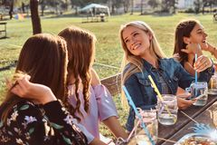 Group of happy girlfriends sitting at the table together celebrating a birthday at the outdoor park. royalty free stock image