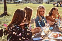 Group of happy girlfriends sitting at the table together celebrating a birthday at the outdoor park. royalty free stock photos