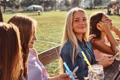Group of happy girlfriends sitting at the table together celebrating a birthday at the outdoor park. stock photography