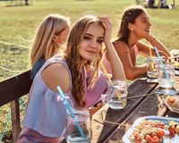 Group of happy girlfriends sitting at the table together celebrating a birthday at the outdoor park. royalty free stock photo