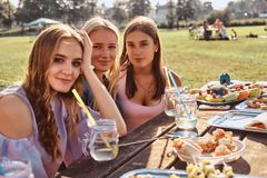 Group of happy girlfriends sitting at the table together celebrating a birthday at the outdoor park. stock image