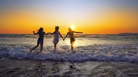 Group of happy girls jump into the ocean at sunset stock images