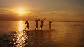Group of happy girls running and playing in water at the beach on sunset dancing, spraying over summer sunset. Beach