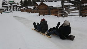Group of happy guys rolls down from icy hill on wooden skiing. stock footage