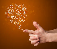 Group of happy hand drawed smiley faces coming out. Of gun shaped hands Stock Photo