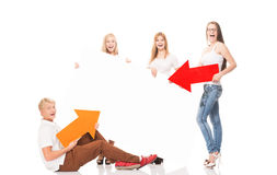 Group of happy and happy teenagers holding arrows. Group of happy teenagers holding arrows on a white billboard background Royalty Free Stock Images