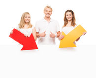 Group of happy and happy teenagers holding arrows. Group of happy teenagers holding arrows on a white billboard background Royalty Free Stock Image
