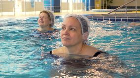 Group of senior women doing aqua aerobics exercises in the swimming pool. Group of happy healthy senior women doing aqua aerobics exercises in the swimming pool stock video footage