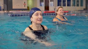 Group of senior women doing aqua aerobics exercises in the swimming pool. Group of happy healthy senior women doing aqua aerobics exercises in the swimming pool stock video