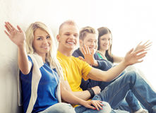Group of happy hipster students on a break. Teenagers waving hands Stock Photography
