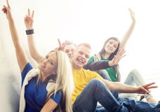Group of happy hipster students on a break. Teenagers waving hands Stock Photos