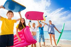 Group of happy kids came to swim on sandy beach. Holding body boards above their heads and lifting swimming sticks, inflatable ring Stock Photo