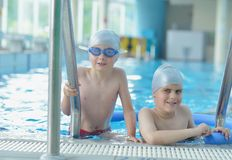 Group of happy kids children at swimming pool. Class learning to swim stock photo