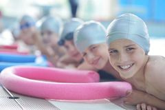Group of happy kids children at swimming pool. Class learning to swim royalty free stock images