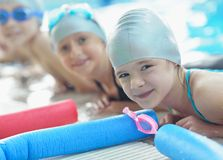 Group of happy kids children at swimming pool. Class learning to swim royalty free stock photography