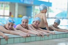 Group of happy kids children at swimming pool. Class learning to swim royalty free stock image