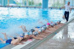 Group of happy kids children at swimming pool. Class learning to swim stock photography