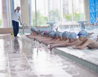 Group of happy kids children at swimming pool. Class learning to swim royalty free stock photos
