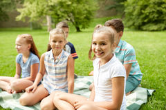 Group of happy kids or friends outdoors. Friendship, childhood, leisure and people concept - group of happy kids or friends sitting on grass in summer park Stock Images