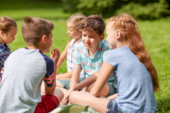 Group of happy kids or friends outdoors. Friendship, childhood, leisure and people concept - group of happy kids or friends sitting on grass in summer park Stock Photos